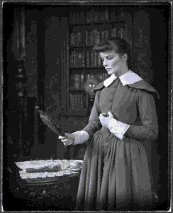 Image of Jane Eyre: Katharine Hepburn as Jane Eyre, standing and looking into hand mirror