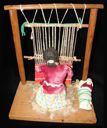Image of Doll Weaving at Loom